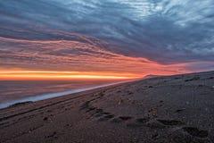 在巴塔哥尼亚海滩的红色日出 库存照片