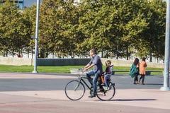 在巴塞罗那生运载他的自行车的年轻儿子 图库摄影
