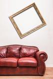 在死墙前面的豪华红色皮革长沙发 免版税库存照片