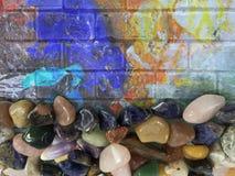 在绘画墙壁上的各种各样的美丽的宝石 库存图片