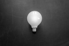 在黑墙壁上的白色表面无光泽的电灯泡 免版税图库摄影