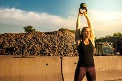 在水壶响铃摇摆顶部的妇女与强的太阳 库存照片