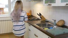 在水壶的妇女倾吐的水和在家准备咖啡早晨 股票录像