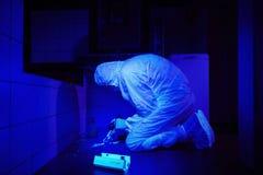 在紫外光下的技术员探索的踪影 免版税库存照片
