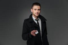 在黑外套的给空白的名片的商人和领带 库存照片