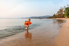 在水外面的小女孩与救生圈 免版税库存图片