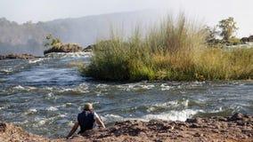 在维多利亚瀑布,赞比亚供以人员在赞比西河边的设置 库存图片