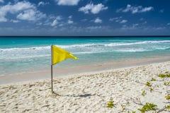 在巴巴多斯海滩的黄色小心旗子 免版税库存照片