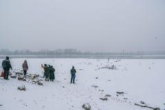 在冻多瑙河的人哺养的鸟有被抓住的bo的 免版税图库摄影
