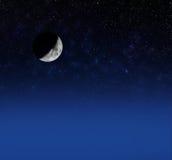 在满天星斗的天空的新月形月亮 免版税库存照片