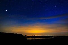在满天星斗的背景天空的早晨黎明在水中反射了 免版税图库摄影