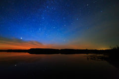 在满天星斗的背景天空的早晨黎明在水中反射了 库存照片