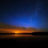 在满天星斗的背景天空的早晨黎明在水中反射了 图库摄影