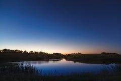 在满天星斗的背景天空的早晨黎明在水o中反射了 库存照片