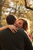在年轻夫妇之间的浪漫亲吻在森林 免版税库存照片