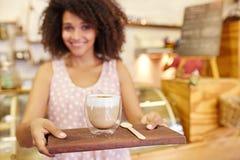 在年轻女服务员运载的一个木盘子的拿铁 免版税图库摄影