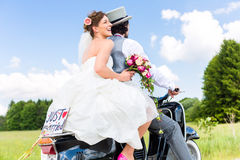 在结婚的小型摩托车的婚礼夫妇 库存照片