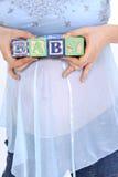 在婴孩之上腹部阻拦期待妈妈s拼写 免版税库存照片