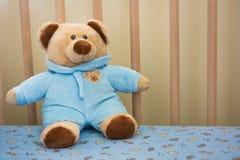 在婴孩小儿床的逗人喜爱的玩具熊填充动物玩偶 图库摄影