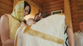 在婴孩脖子的教士礼服十字架在洗礼以后仪式  影视素材