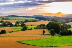 在绵延山乡下风景的美好的日落有太阳的放光贯穿的天空和照明设备山坡 库存照片