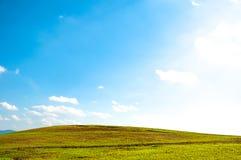 在绵延山的宽绿色领域和与云彩的蓝天 免版税库存图片