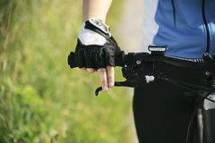 在登山车的少妇训练和循环在公园 免版税库存图片