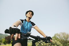在登山车的少妇训练和循环在公园 免版税库存照片