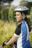 在登山车的少妇训练和循环在公园 免版税图库摄影