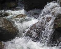 在黑岩石中的山河 在石头的淡水快速的小河 免版税图库摄影