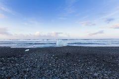 在黑岩石沙子海滩海岸地平线的小冰 免版税图库摄影