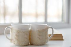 在围巾的两个白色杯子在一张桌上在一个窗口的背景中站立与咖啡舒适芳香的  免版税库存图片