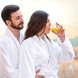 在浴巾饮用的果汁的夫妇 免版税库存图片