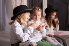 在黑帽会议饮料牛奶的孩子。 免版税库存照片