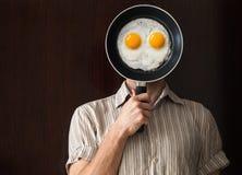 在黑平底锅后的年轻人画象用鸡蛋 库存照片