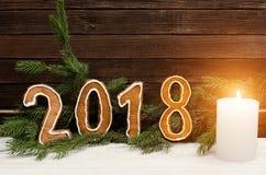 在2018年图在云杉的分支和木墙壁,白色蜡烛背景的姜饼中  免版税库存照片