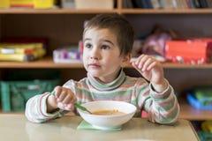 在4年岁吃汤的一个男孩在幼儿园 库存图片