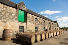 在仓库前面的威士忌酒桶 库存照片