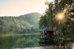 在水库旁边的村庄平静在日落 库存图片