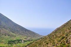 在2座山之间的谷与海洋在背景中 免版税库存图片