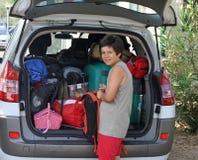 在离开期间,人在汽车的行李投入袋子 免版税图库摄影