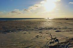 在离开的宽海滩的黄昏与在海洋的小船 免版税库存图片