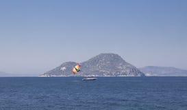 在离开的海的一条小白色小船反对一个小海岛 图库摄影
