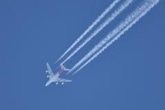 在离开空白线路的蓝天的飞行飞机后边 库存图片