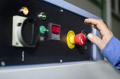 在紧急刹车按钮的手 库存图片