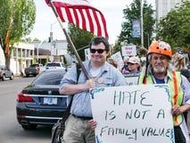 在`怨恨的微笑的人举行旗子不是家庭价值观`签字在集会 免版税库存照片