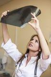 在年轻患者里屋子白色制服的医治妇女 免版税库存图片