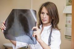 在年轻患者里屋子白色制服的医治妇女 图库摄影