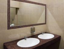在洗手间公共厕所的一个大镜子 库存图片