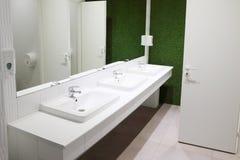 在洗手间的三个白色水槽与大镜子 免版税库存图片